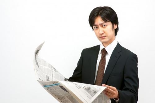 新聞を読んで情報収集をする飯田さん