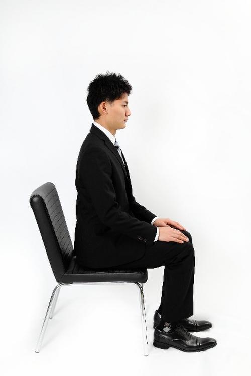 スーツ姿で座る男